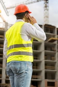 Foto da vista traseira do empresário com capacete de segurança e colete de segurança falando por telefone no canteiro de obras