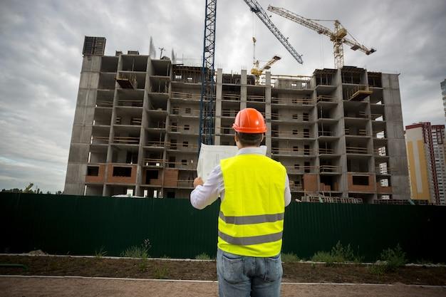 Foto da vista traseira do engenheiro com capacete e colete de segurança lendo plantas no canteiro de obras