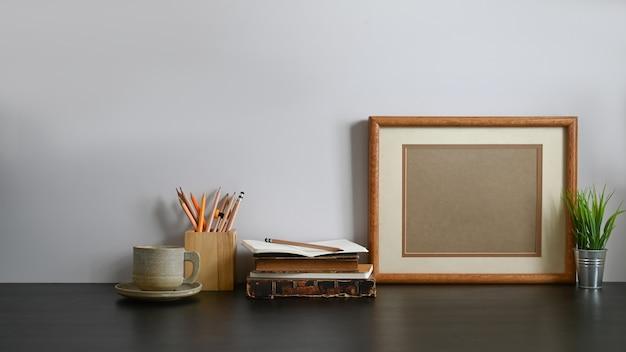 Foto da xícara de café, porta-lápis de madeira, livro antigo, lápis, porta-retrato e vaso de plantas, todos estes estão reunidos na mesa de madeira preta com parede cinza