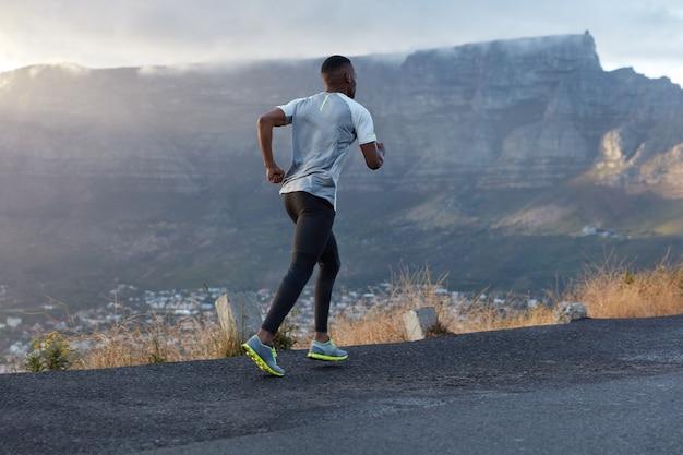 Foto das costas de um homem ativo de pele escura em ação, atravessa uma estrada de montanha, leva um estilo de vida saudável, tem resistência e motivação para estar em forma, posa sobre a montanha, gosta da natureza