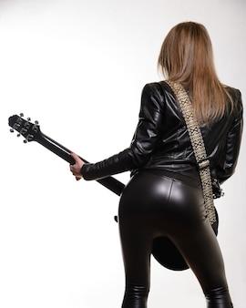 Foto das costas de uma guitarrista em jaqueta de couro