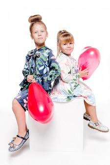 Foto de 2 meninas com vestidos elegantes sentadas com bolsas grandes com balões em forma de coração dentro