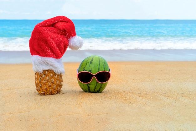 Foto de abacaxi com chapéu de papai noel e melancia alegre verde em óculos de sol na praia tropical.