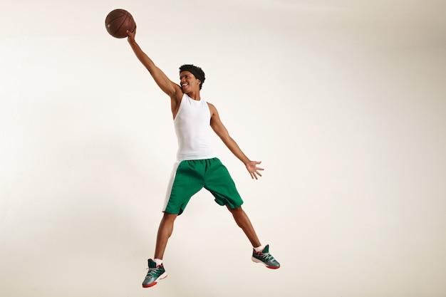 Foto de ação de um jovem atleta negro feliz vestindo camisa branca e shorts verdes pulando alto para pegar uma bola de basquete vintage em branco