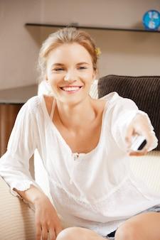 Foto de adolescente feliz com controle remoto de tv