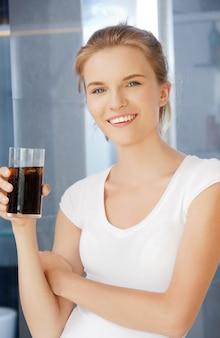 Foto de adolescente feliz e sorridente com um copo de coca-cola