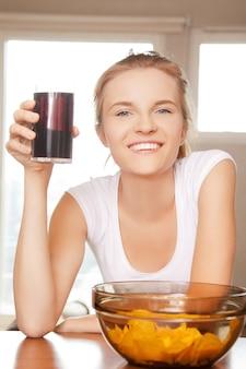Foto de adolescente sorridente com batatas fritas e coca