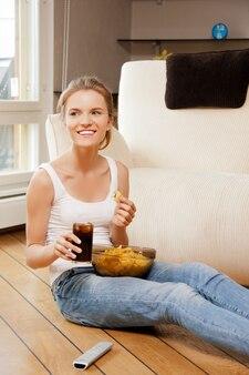 Foto de adolescente sorridente com controle remoto