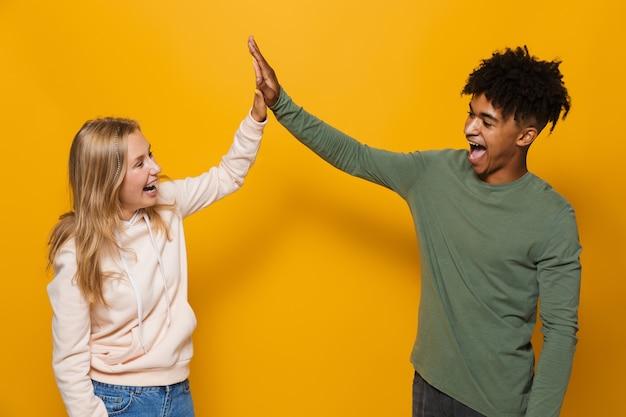 Foto de adoráveis alunos, homem e mulher de 16 a 18 anos, com aparelho dentário, rindo e dando mais cinco, isolado sobre um fundo amarelo