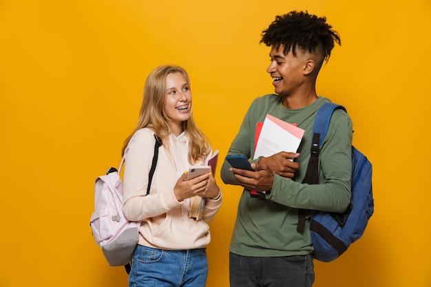 Foto de adoráveis alunos, homem e mulher de 16 a 18 anos, usando mochilas, sorrindo, segurando cadernos e usando telefone celular, isolada sobre fundo amarelo