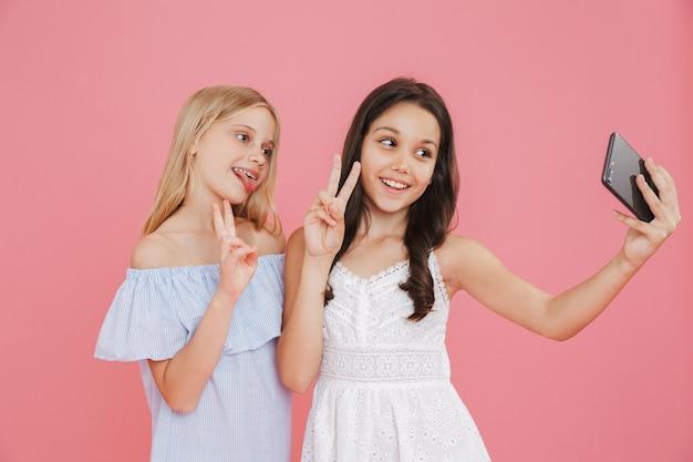 Foto de adoráveis garotas morenas e loiras usando vestidos sorrindo e mostrando o símbolo da paz enquanto tomam uma selfie no celular, isolada sobre fundo rosa