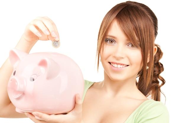 Foto de adorável adolescente com cofrinho e moeda