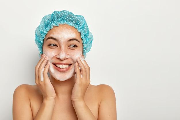 Foto de adorável jovem aplica espuma para limpar o rosto, toca as bochechas, lava pela manhã, sente-se relaxada e feliz, faz tratamentos refrescantes