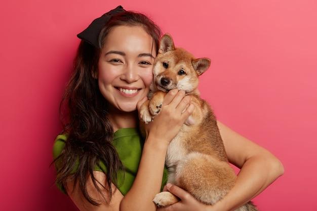 Foto de adorável jovem com sorriso dentuço, abraça e faz foto com linda cachorra shiba inu obediente, gosta de brincar com amiga de quatro patas.