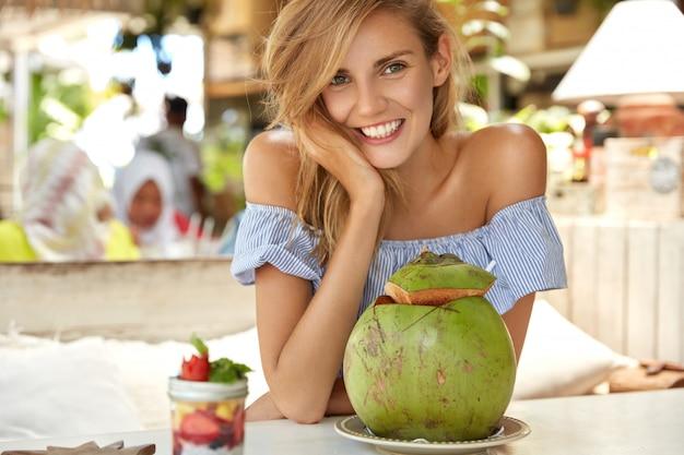 Foto de adorável jovem sorridente relaxado feminino na blusa da moda, aproveita o tempo livre e a recreação no café, bebe um coquetel de coco, tem uma expressão feliz. turista relaxada viaja para o exterior