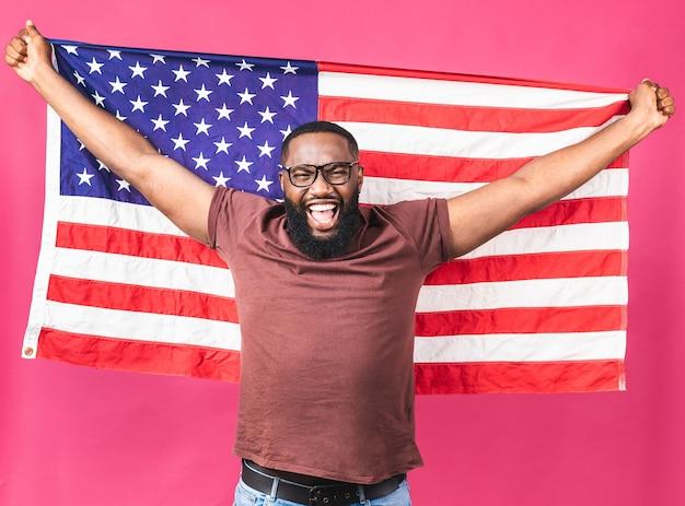 Foto de alegre americano africano homem manifestante levantar bandeira nacional americana revolução de pessoas negras amam todos os seres humanos expressam solidariedade de unidade isolada sobre fundo rosa.