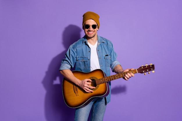 Foto de alegre atraente na moda bonito e legal cara segurando uma guitarra com as mãos em forma de chapéu tocando um instrumento de músico isolado sobre um fundo roxo de cor vibrante