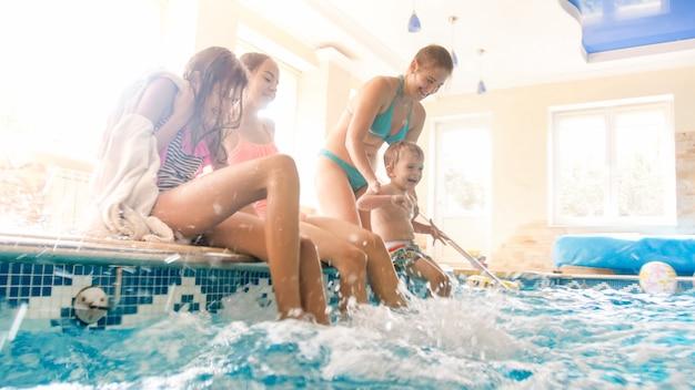Foto de alegre família rindo com crianças espirrando água com os pés na piscina coberta. família brincando e se divertindo na piscina