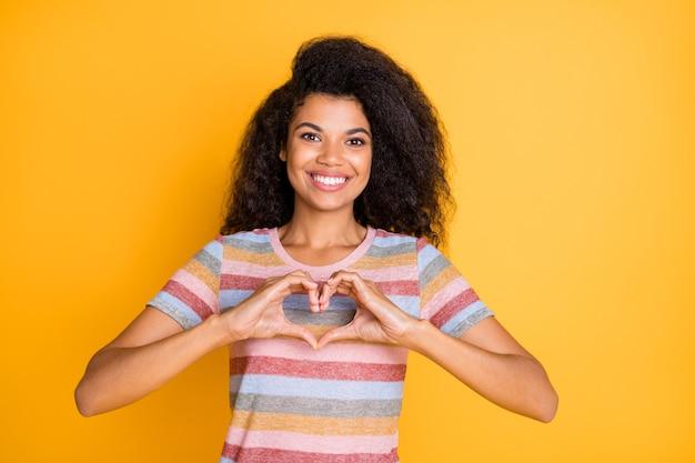 Foto de alegre garota afro-americana mostrando o símbolo do coração com os dedos