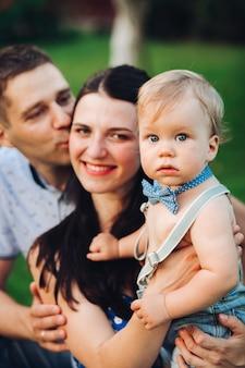 Foto de alegre mãe caucasiana, pai e filho se divertindo juntos e sorrindo no jardim