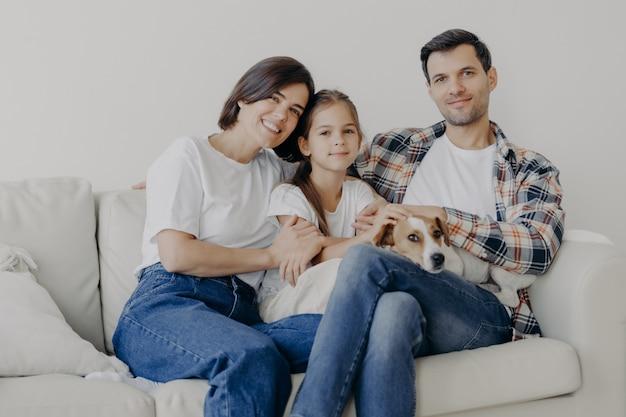 Foto de alegre marido e mulher passam o tempo livre com sua adorável filha