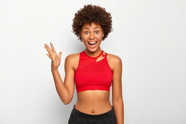 Foto de alegre mulher de pele escura levanta a palma da mão, usa sutiã esportivo vermelho, mostra a barriga, tem um penteado afro, posa interior sobre fundo branco.