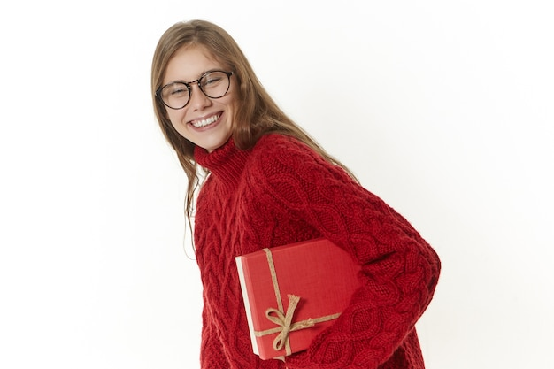 Foto de alegre mulher jovem e atraente de óculos e suéter carregando um presente em uma caixa vermelha e sorrindo amplamente
