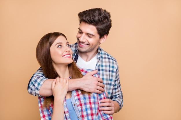 Foto de alegre positivo fofo charmoso lindo casal de duas pessoas se abraçando, sorrindo, curtindo um ao outro, empresa isolada sobre fundo bege