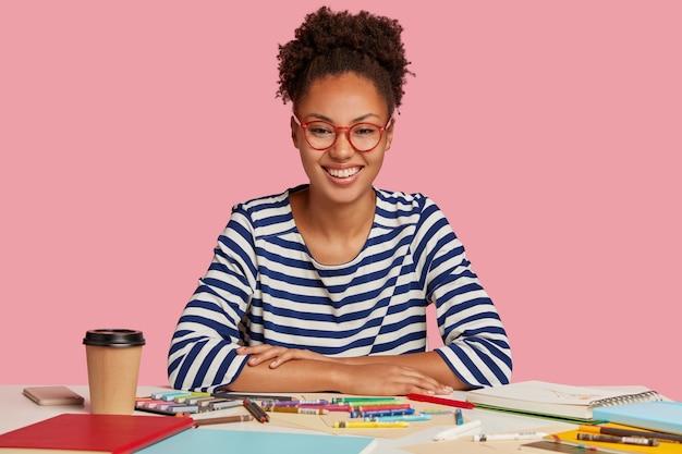 Foto de alegre senhora de pele morena com cabelo afro penteado em rabo de cavalo, tem sorriso dentuço, alegra-se com o bom resultado do trabalho, cria foto em bloco de notas, usa óculos de aro vermelho, isolado no rosa
