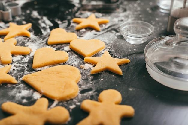 Foto de algumas figuras de pão de gengibre não assado em uma mesa preta com um pouco de farinha.