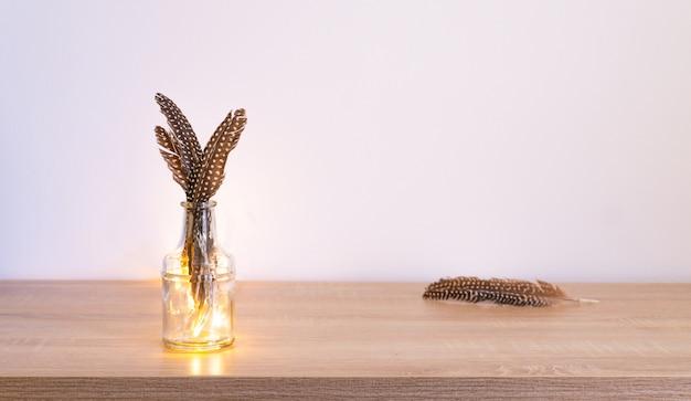 Foto de algumas penas empilhadas e colocadas em um vaso de vidro