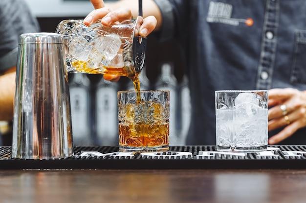 Foto de alta qualidade de coquetel alcoólico marrom com gelo em restaurante