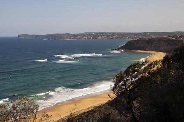 Foto de alto ângulo da costa do oceano com uma pequena praia de areia
