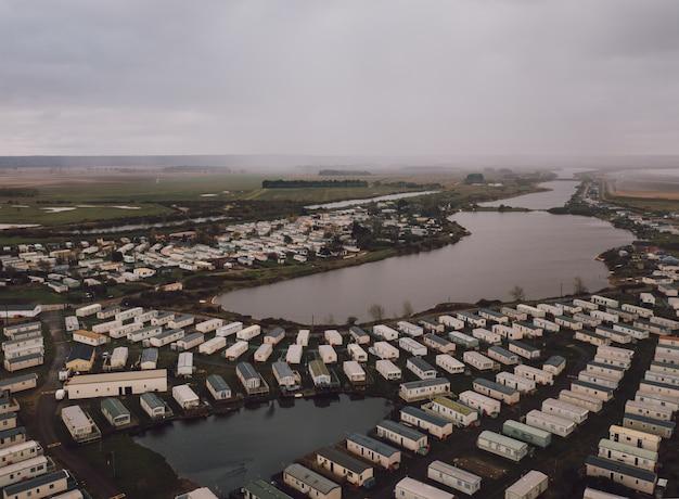 Foto de alto ângulo das casas retangulares nos campos perto de um belo lago nebuloso