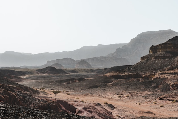 Foto de alto ângulo das colinas em um deserto cercado por montanhas magníficas