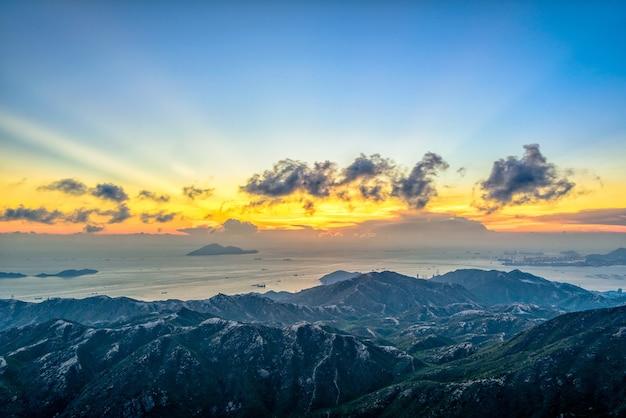 Foto de alto ângulo das montanhas sob as luzes de tirar o fôlego no céu nublado