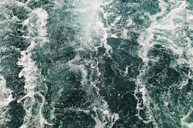 Foto de alto ângulo das ondas do oceano se movendo em direção à costa