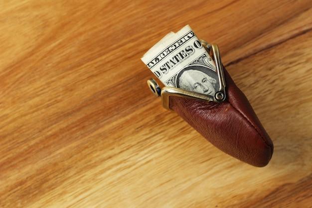 Foto de alto ângulo de algum dinheiro em uma bolsa de couro em uma superfície de madeira