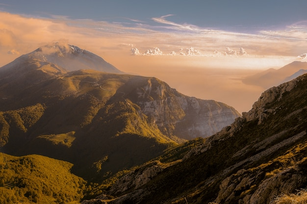 Foto de alto ângulo de belas montanhas verdes cobertas por nuvens sob o céu colorido
