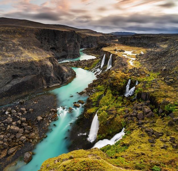 Foto de alto ângulo de cachoeiras na região das terras altas da islândia com um céu nublado e cinza