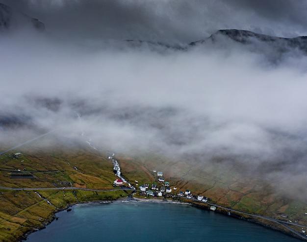 Foto de alto ângulo de casas em uma colina coberta de grama pela água capturada em uma noite de nevoeiro