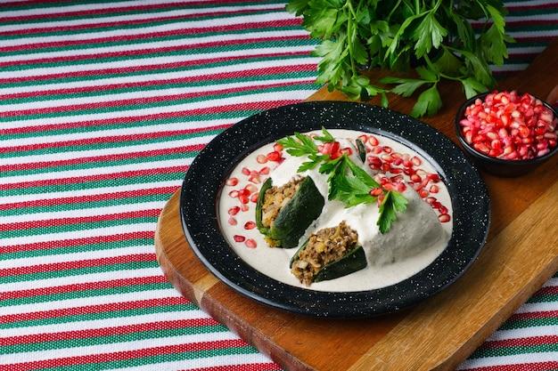 Foto de alto ângulo de chiles en nogada em um prato sobre uma placa de madeira sobre a mesa
