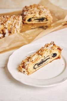 Foto de alto ângulo de deliciosas sementes de papoula pedaço de bolo com cobertura de açúcar branco em uma mesa branca