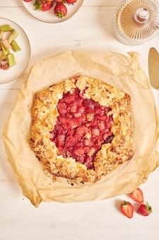 Foto de alto ângulo de delicioso bolo de galata de morango e ruibarbo com ingredientes em uma mesa branca