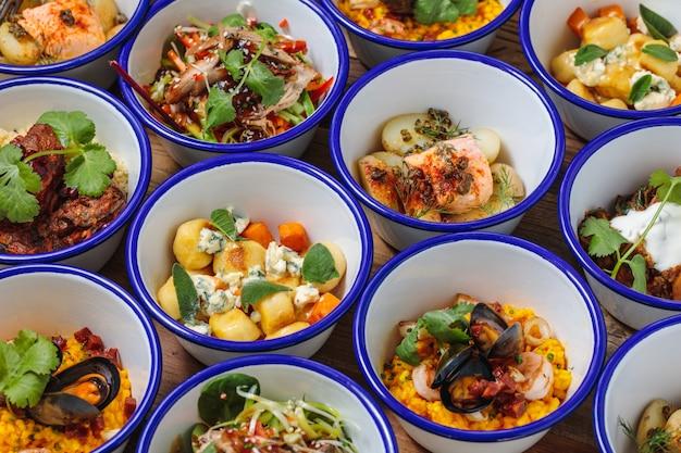 Foto de alto ângulo de diferentes pratos perto um do outro em uma mesa de madeira