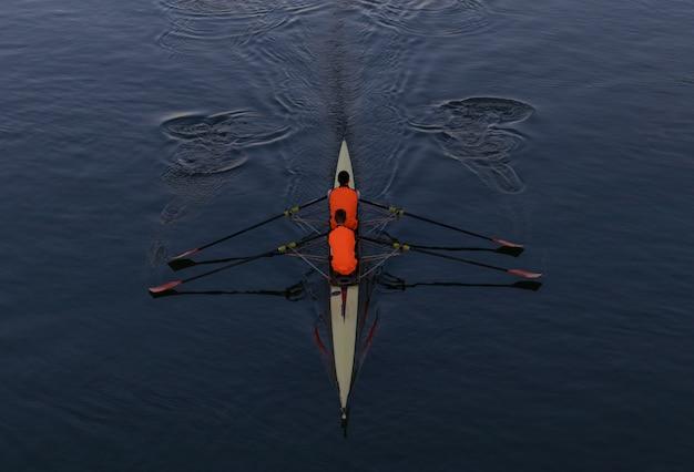 Foto de alto ângulo de duas pessoas remando em um barco no meio do mar