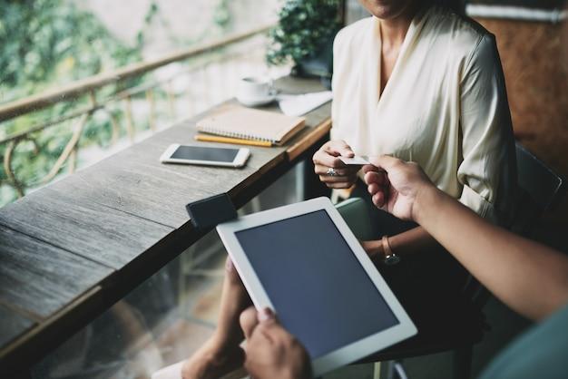 Foto de alto ângulo de garçom irreconhecível com tablet aceitando cartão de crédito da mulher no café
