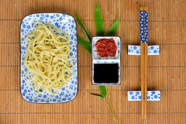 Foto de alto ângulo de macarrão e molhos em pratos brancos e pauzinhos em uma tampa de mesa de bambu