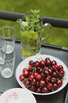 Foto de alto ângulo de prato de cerejas perto de limonada de menta em uma mesa preta
