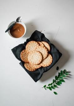 Foto de alto ângulo de salgadinhos e uma tigela de caramelo em uma superfície branca